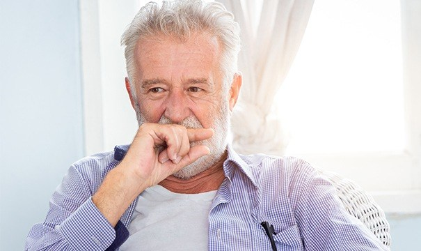 sneior man covering mouth in need of dentures