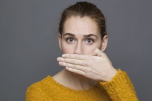 woman covering her mouth bad breath