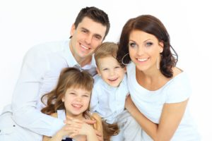 Young family smiling after seeing dentist in Attleboro.