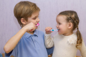 Children clean teeth with brushing tips from their dentist.