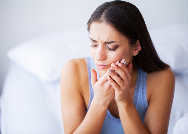Woman experiencing tooth sensitivity