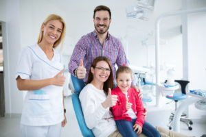 Family and dentist giving thumbs up