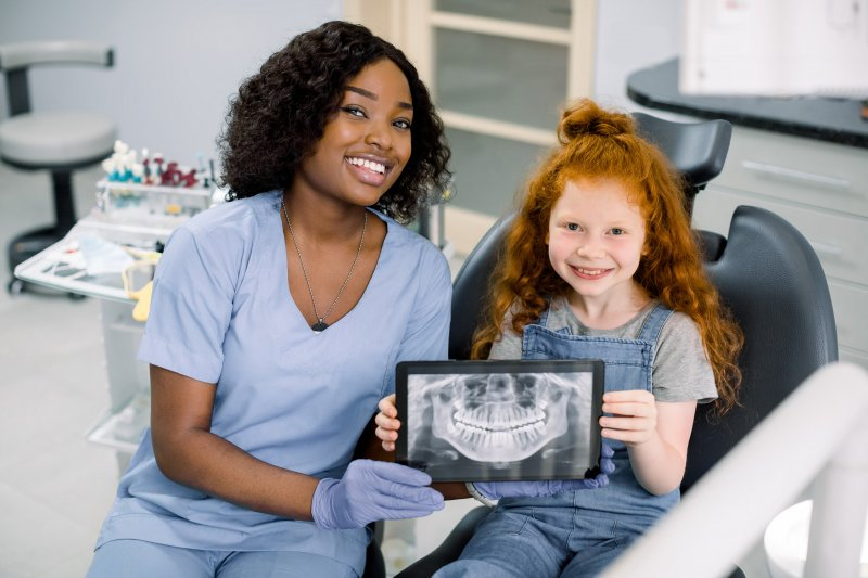 a child holding a tablet with her dental x-rays in Attleboro
